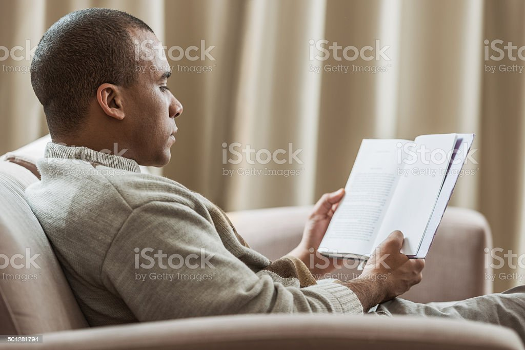 Profile of African America man reading book at home. stock photo