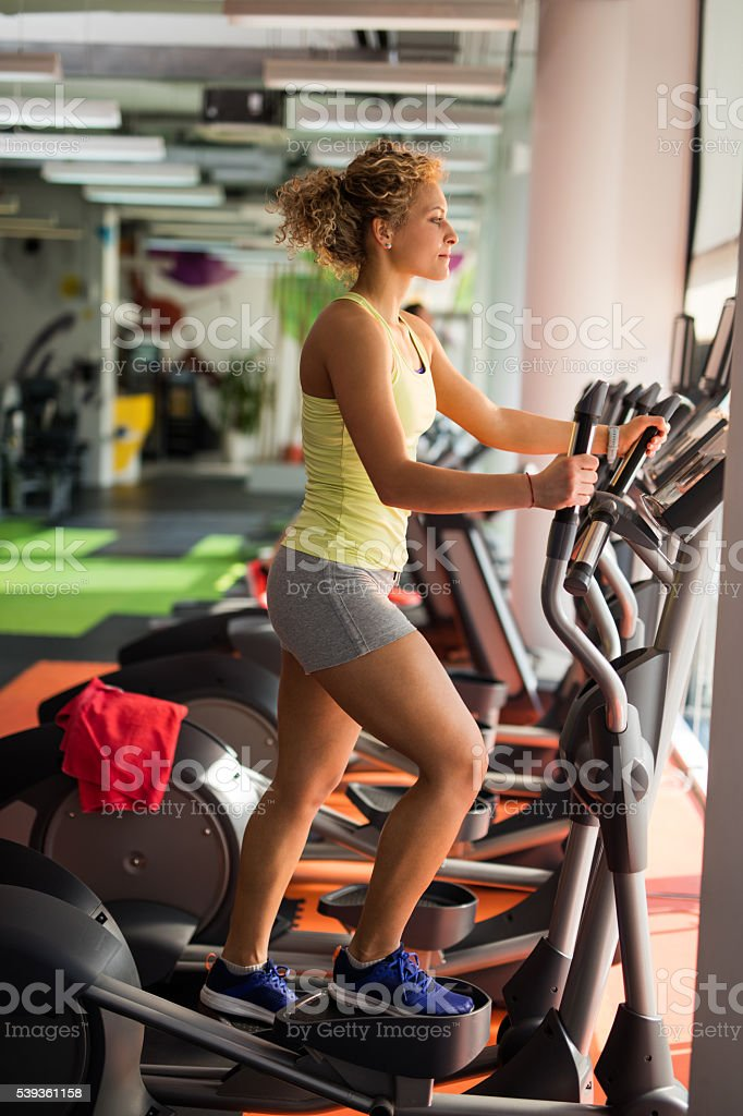 Profile of athletic woman exercising on stair climbing machine. stock photo
