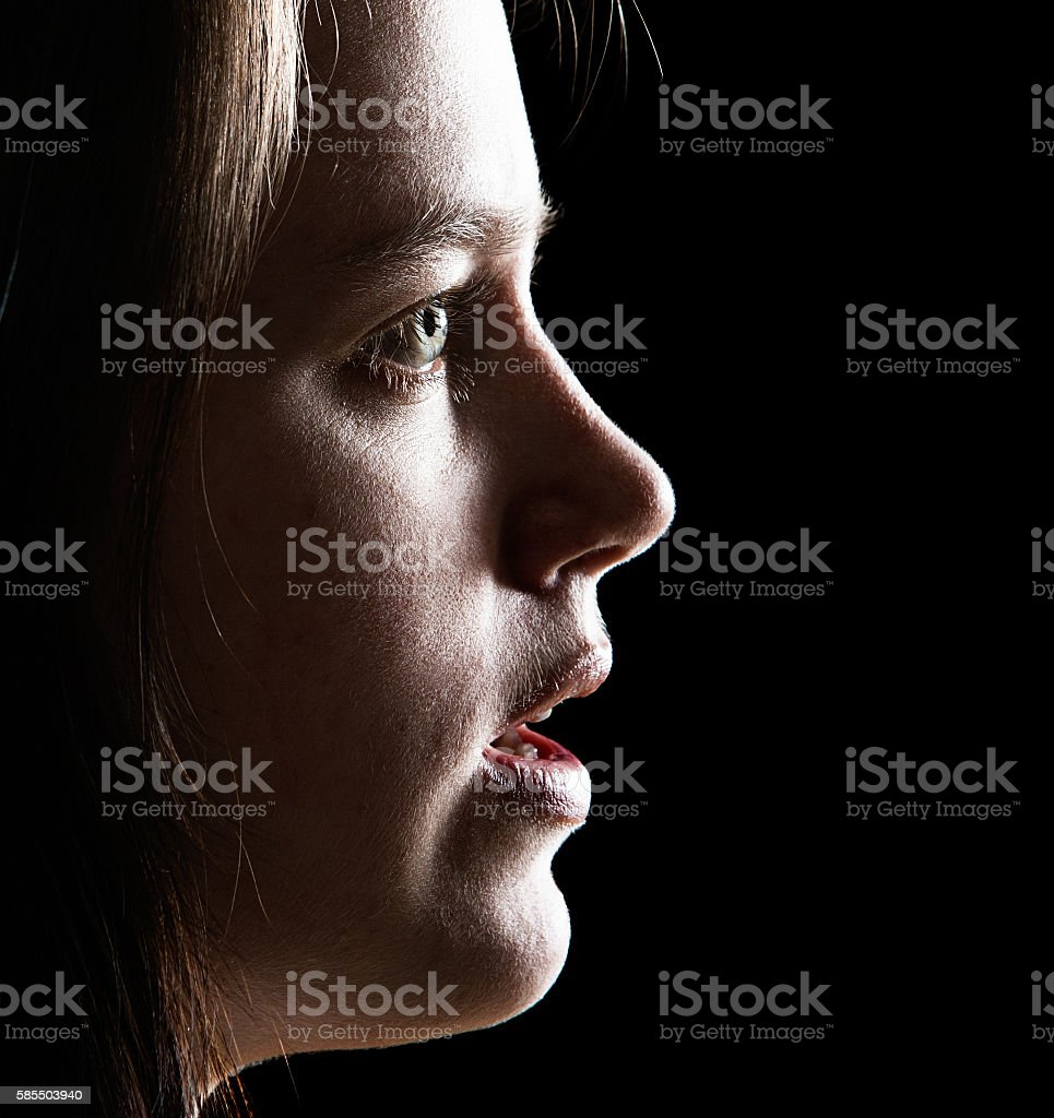 Profile of beautiful but anxious young woman stock photo