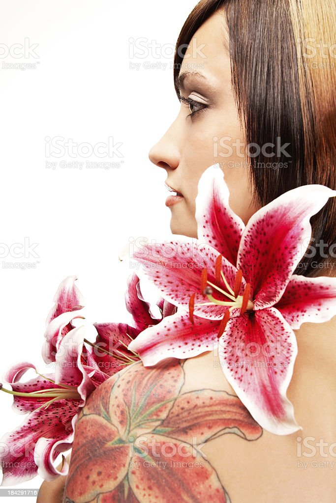 Profile of Beautiful Woman with Stargazer Lilies and Lily Tattoo stock photo