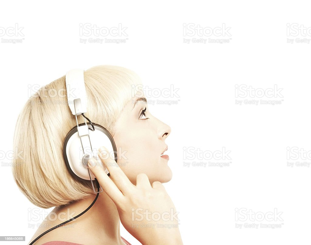 Profile of beautiful young blonde woman with headphones looking up stock photo