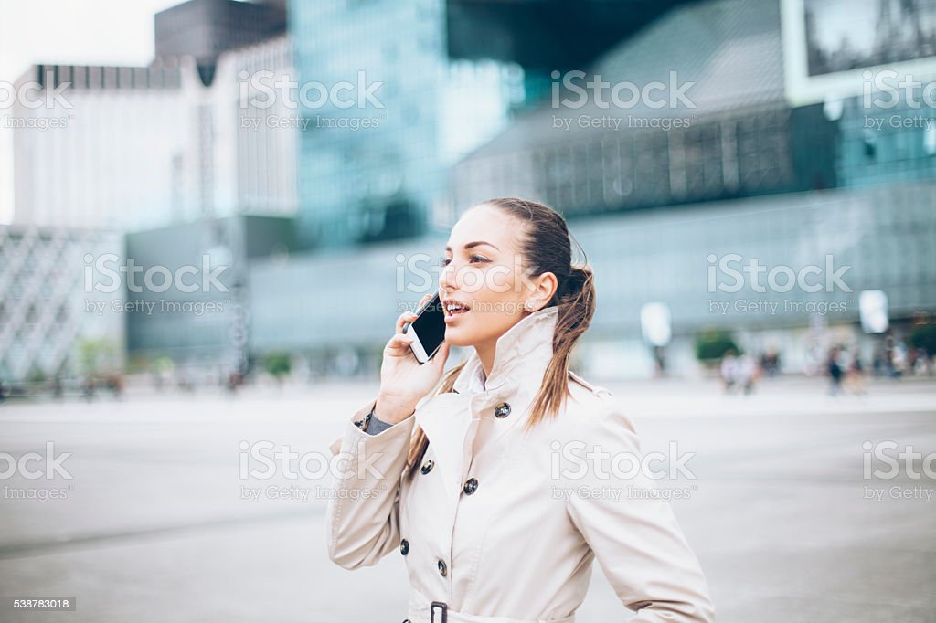 Profile of beautiful young woman talking on phone at street stock photo
