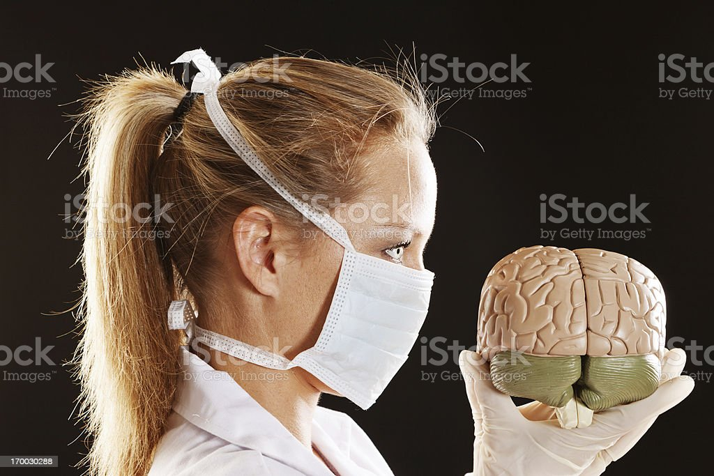 Profile of blonde in surgical mask holding model brain stock photo