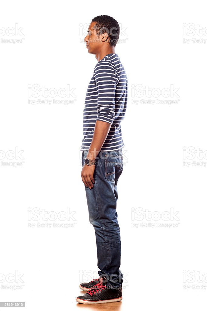 Profile of dark-skinned young man in jeans and blouse stock photo