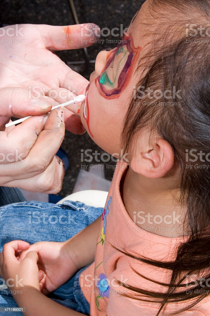 Profile of girl getting her face painted royalty-free stock photo