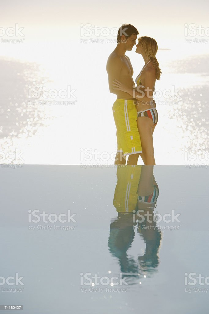 Profile of man and woman in swimsuits embracing outdoors with water royalty-free stock photo
