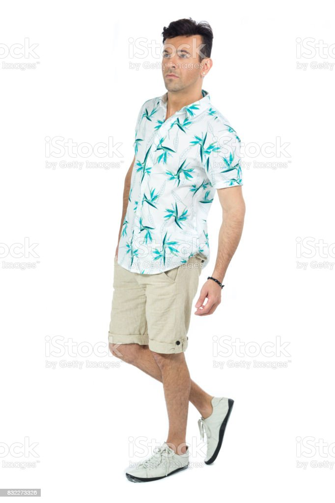Profile of man. Brazilian male wearing a Hawaiian style floral shirt and beige shorts. Summer, tropical. stock photo