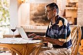 Profile of senior man sitting on terrace and using laptop.