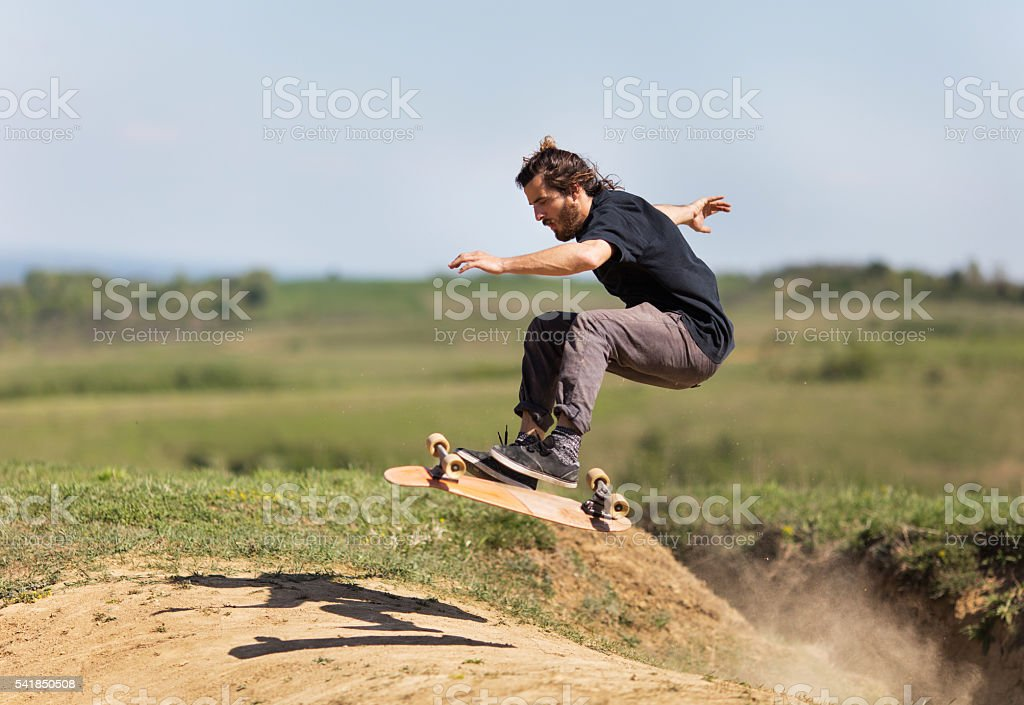 Profile of skateboarder in action on a dirt road. stock photo