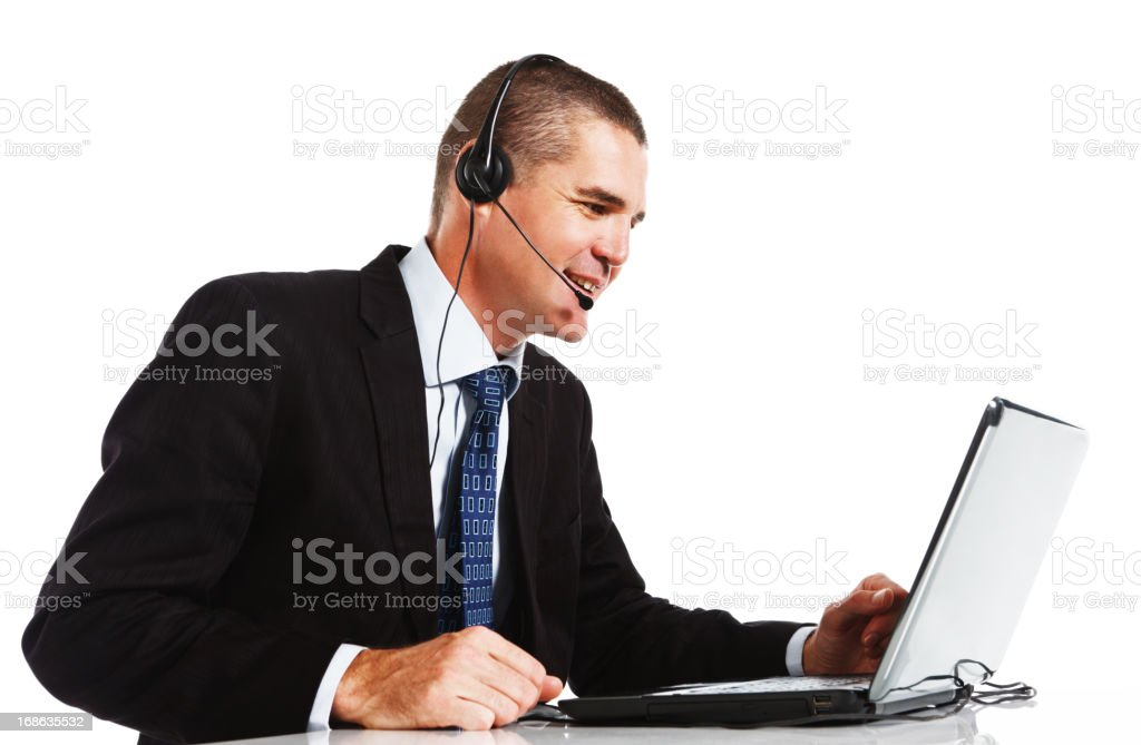 Profile of smiling businessman in headset with laptop royalty-free stock photo