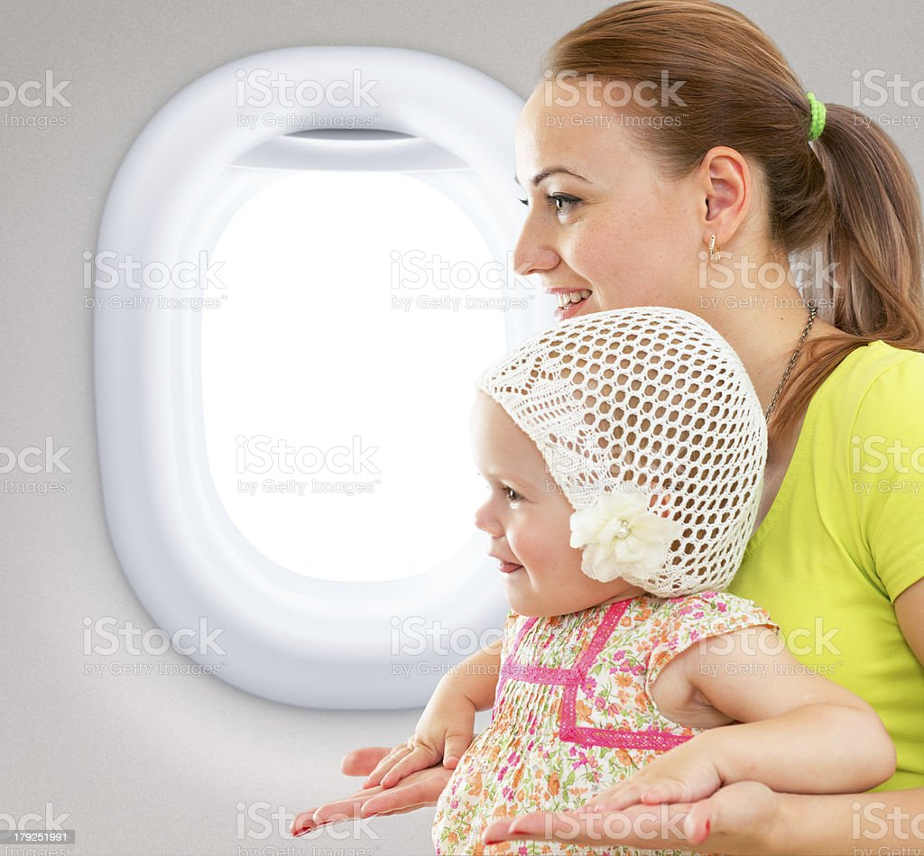 Profile of smiling mother and child in airplane royalty-free stock photo