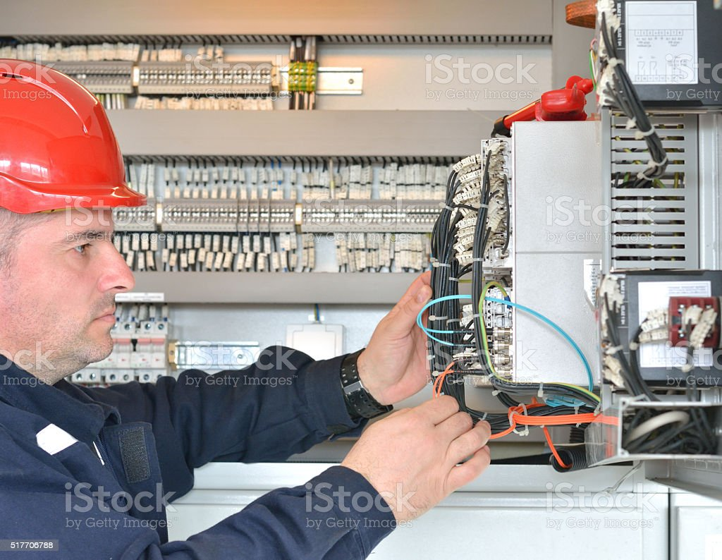 Profile of Tehnician with Red Hardhat Testing Equipment stock photo