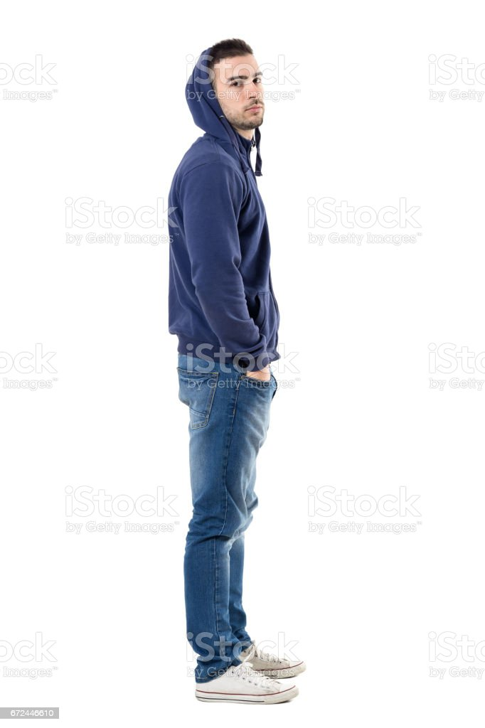Profile of tough young casual man in blue hoodie looking intense at camera stock photo