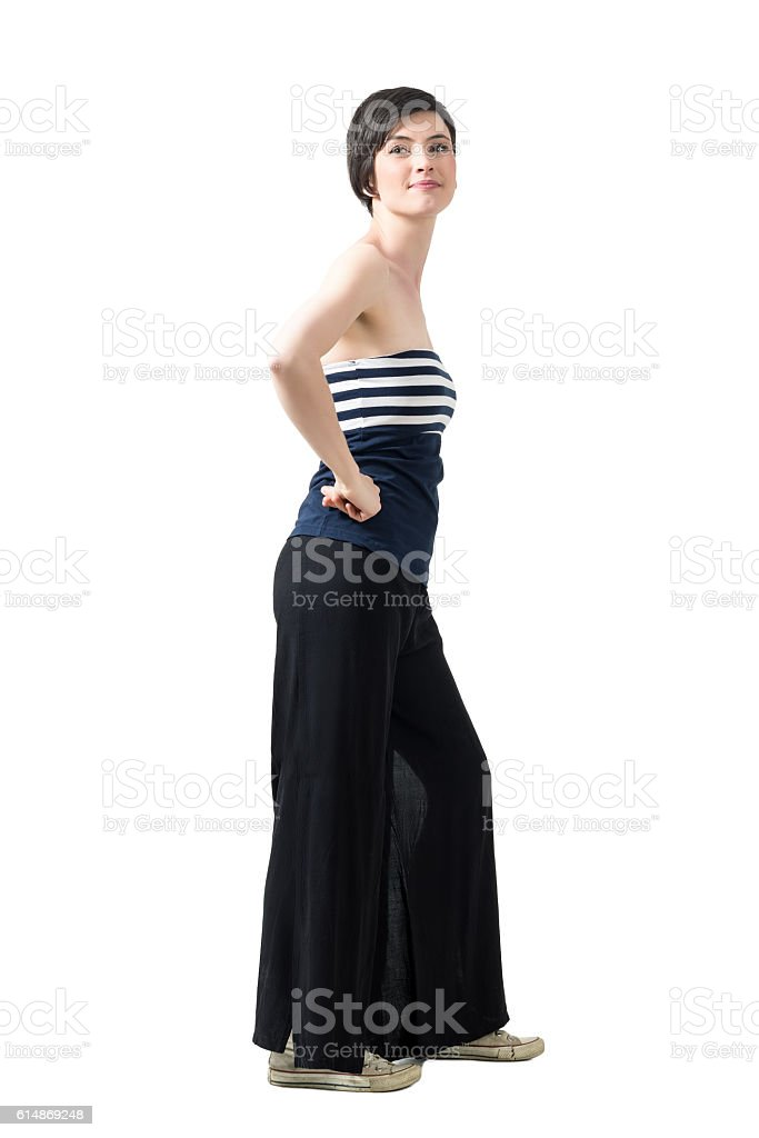 Profile of trendy woman in wide-leg pants and off-the-shoulder top stock photo