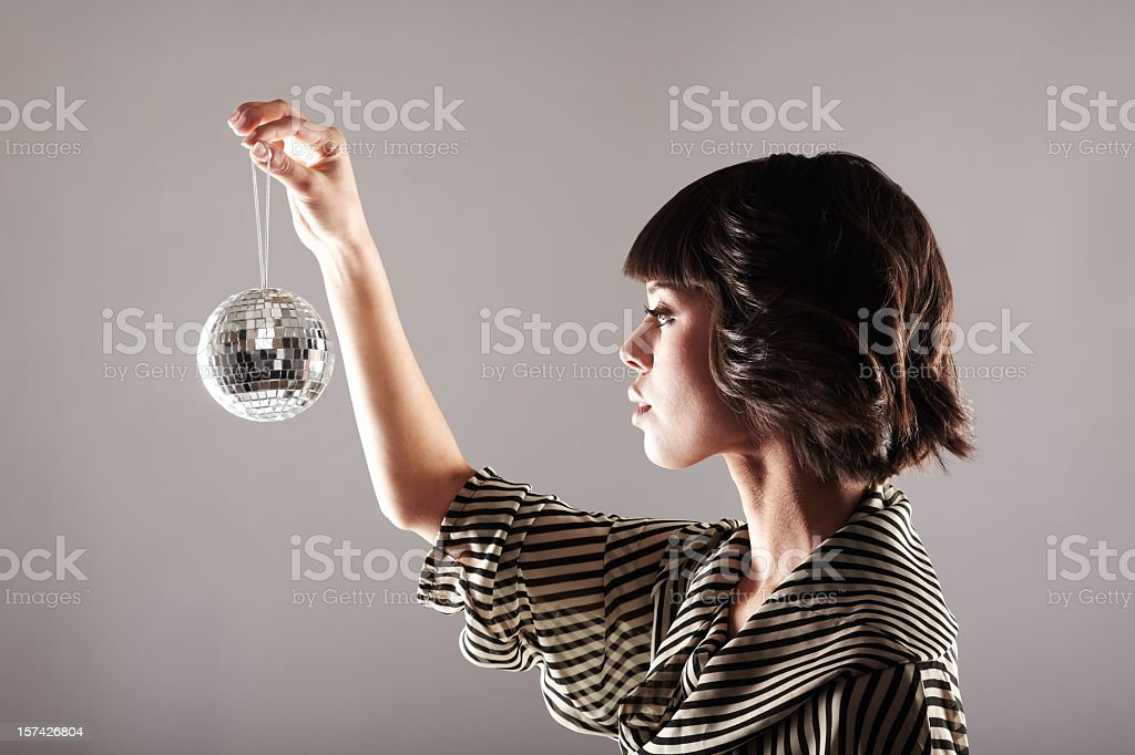 Profile of woman looking at small disco ball royalty-free stock photo