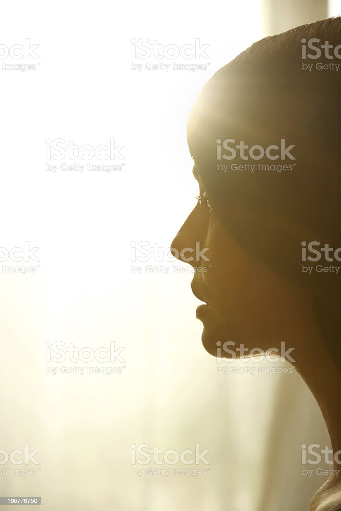 Profile of woman looking towards the light stock photo