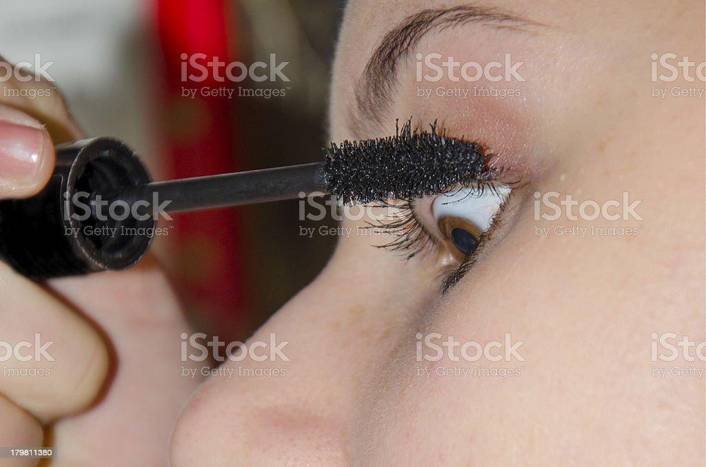 profile of young beautiful teenage girl applying mascara royalty-free stock photo