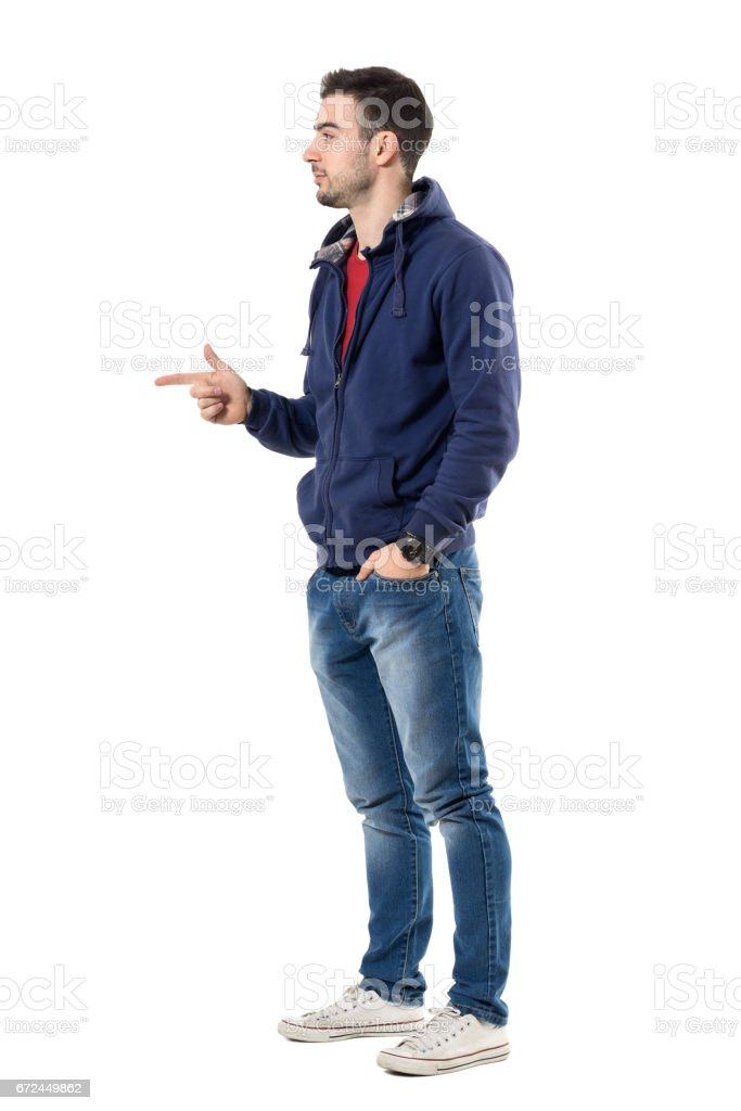 Profile of young casual guy in sweatshirt pointing finger showing copyspace stock photo