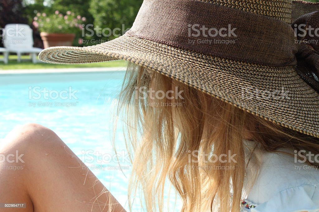 Profile of young girl with hat by a pool royalty-free stock photo