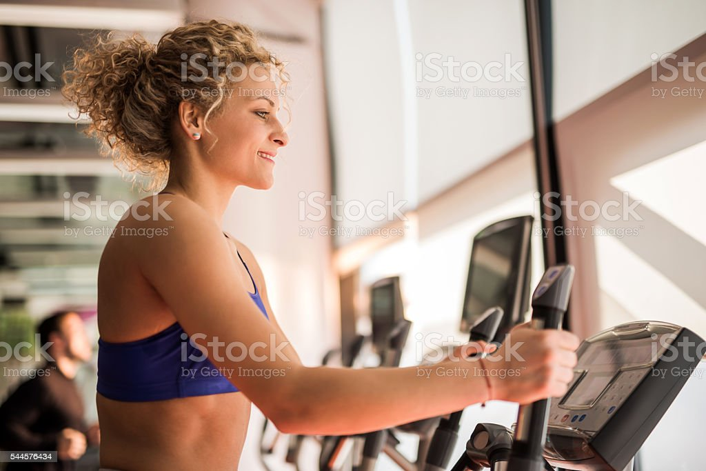 Profile of young smiling woman exercising in health club. stock photo