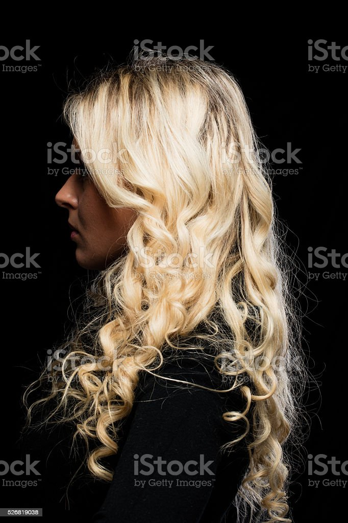 profile portrait of a blonde woman on black stock photo