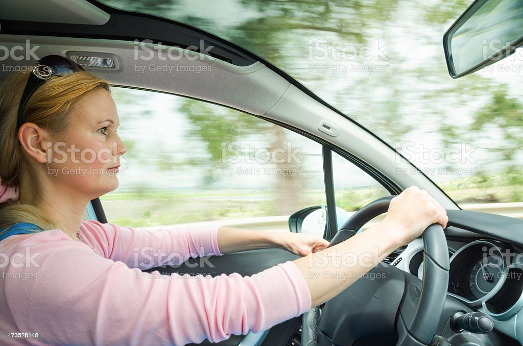 Profile portrait of serious calm woman carefullly safe driving stock photo