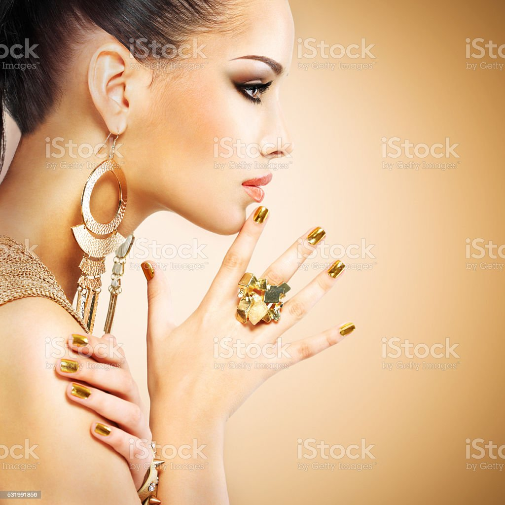 Profile portrait of the fashion woman with beautiful golden mani stock photo