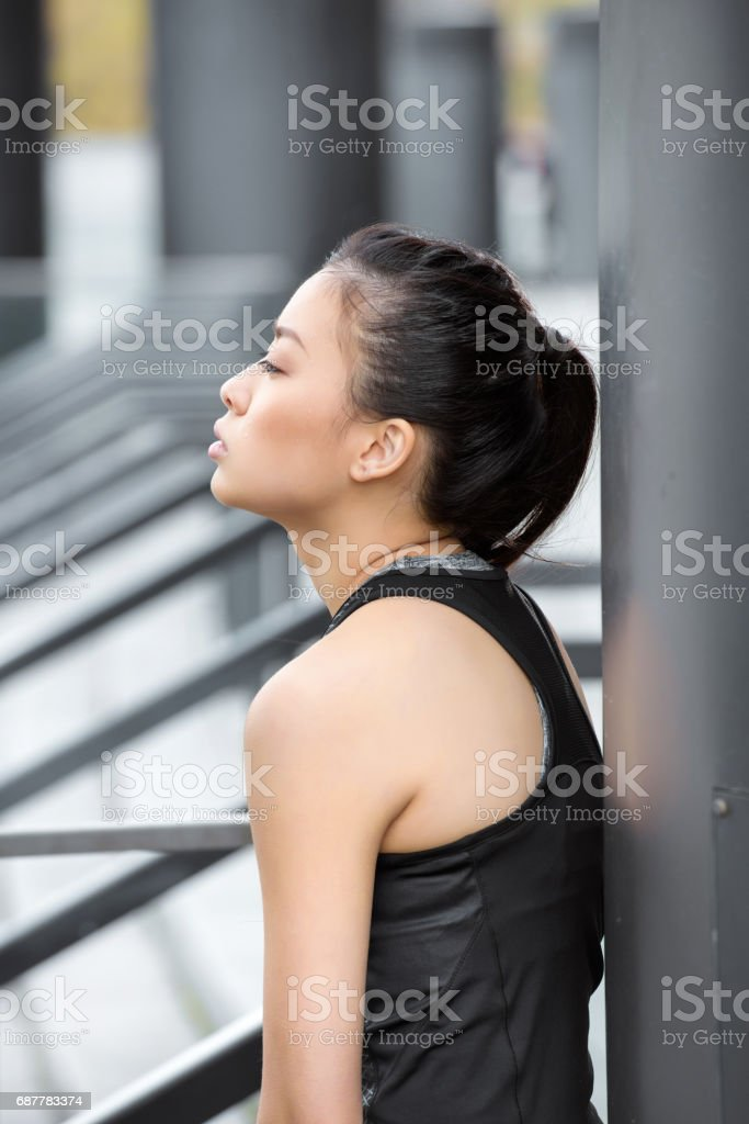 Profile portrait of young brunette sportswoman looking away on stadium stock photo