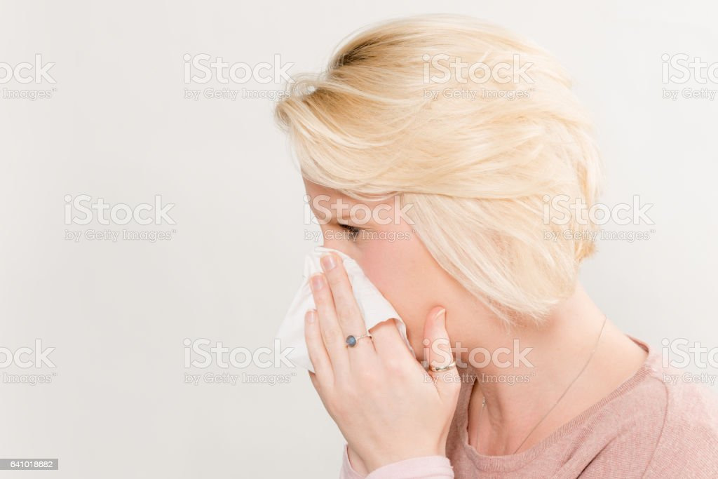 Profile Shot of Lady Pressing Tissue on Nose Copy Space stock photo