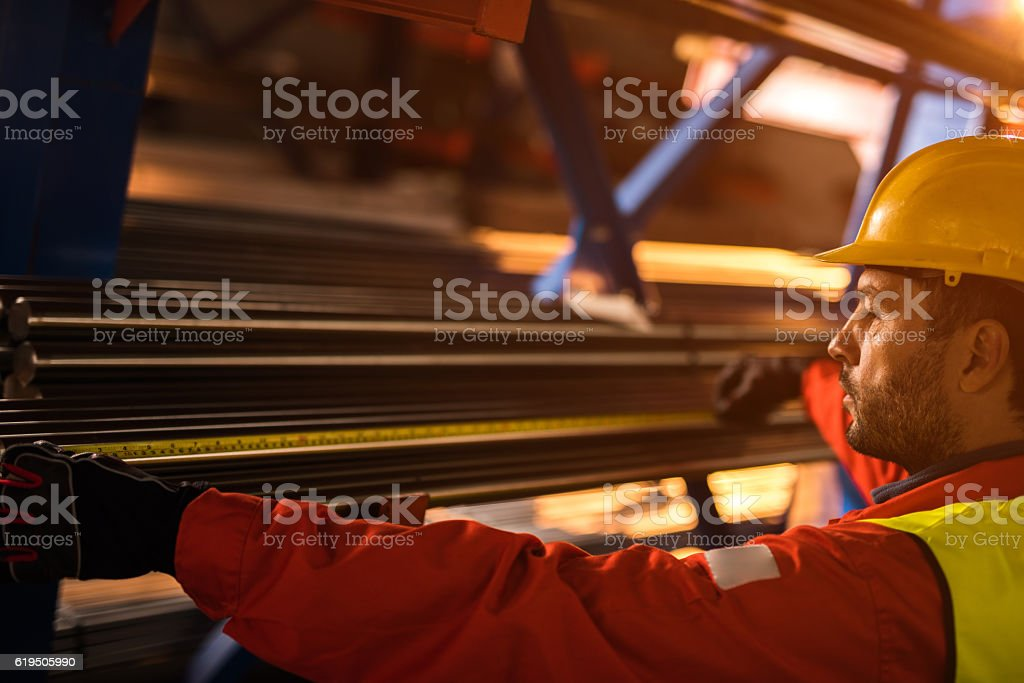Profile view of a worker measuring metal tubes in factory. stock photo
