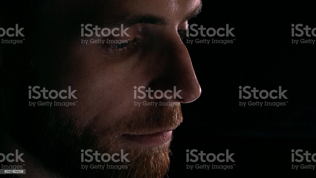 Profile view of focused intelligent bearded young man using his stock photo