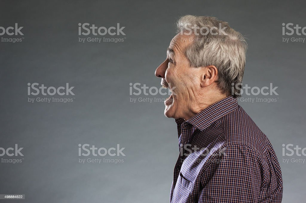 Profile view of male senior shouting. Horizontal portrait on gra stock photo