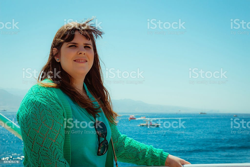 Profile view of one smiling woman looking away at sea stock photo