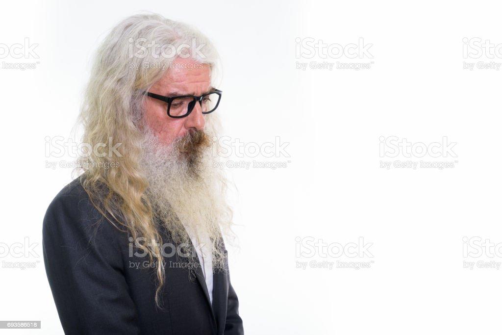 Profile view of sad senior bearded businessman looking down while wearing eyeglasses stock photo