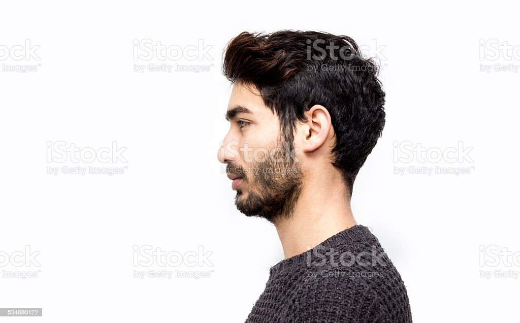 Profile view of serious young man over white background stock photo