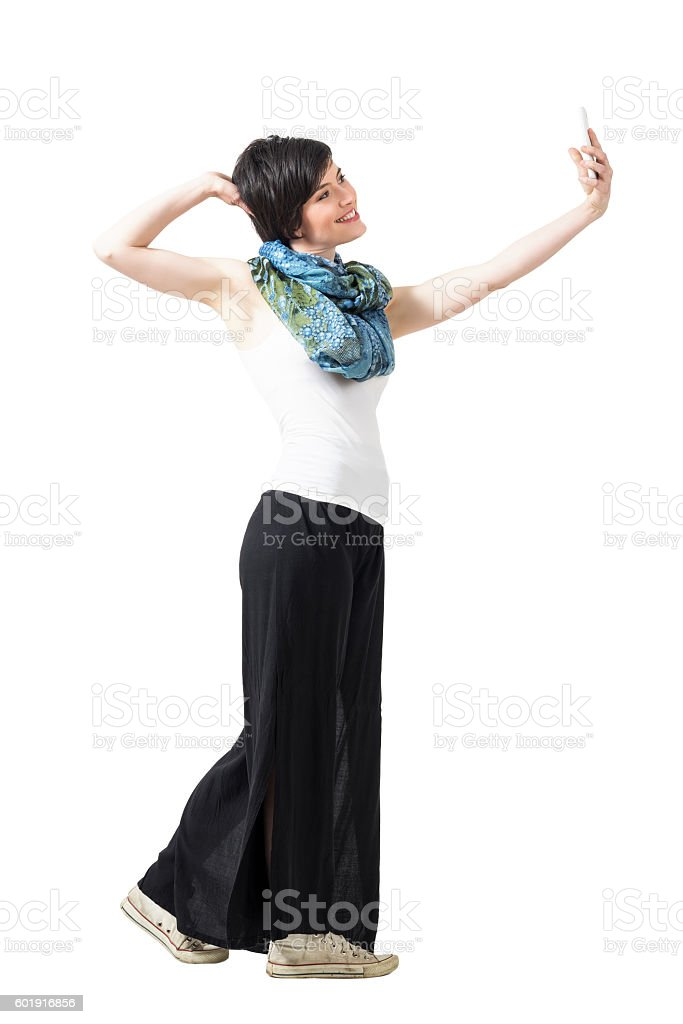 Profile view of young woman posing and taking selfie photo stock photo