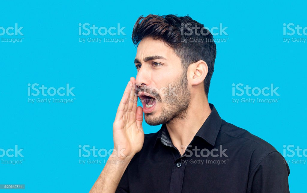 profile view portrait of young man shouting against blue backgro stock photo