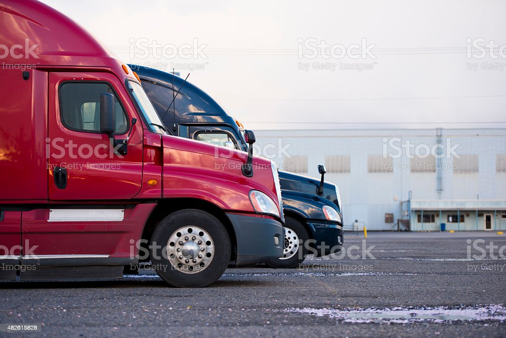 Profiles semi trucks modern color red blue on parking lot stock photo
