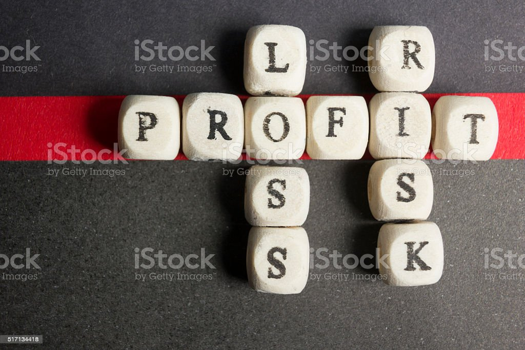 Profit, loss and risk crossword blocks on table. Top view stock photo