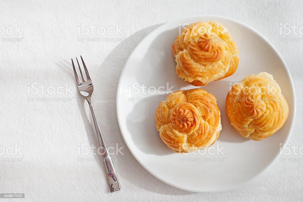 Profiteroles, choux with a custard cream dessert on white plate stock photo