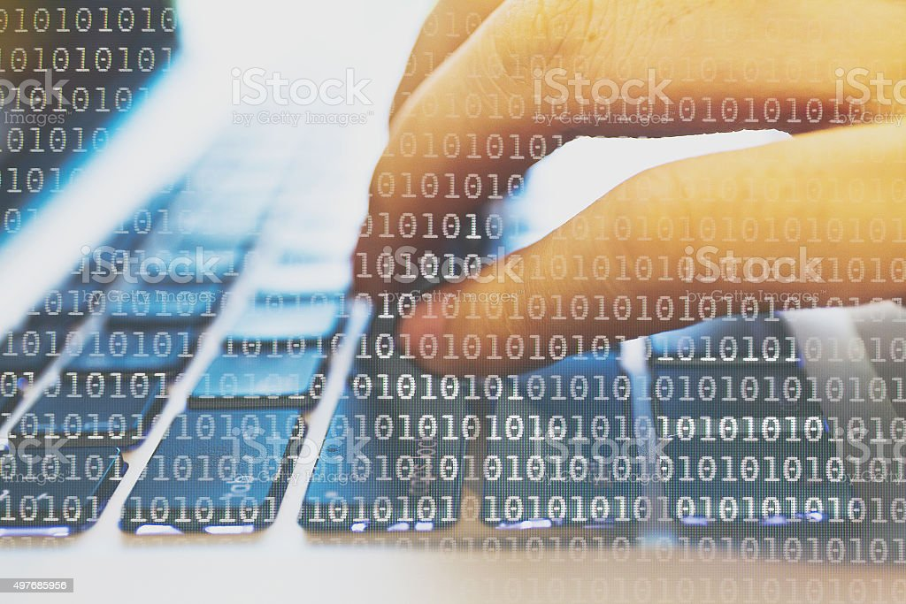 Programmer coding on his laptop dissolved with binary code background stock photo