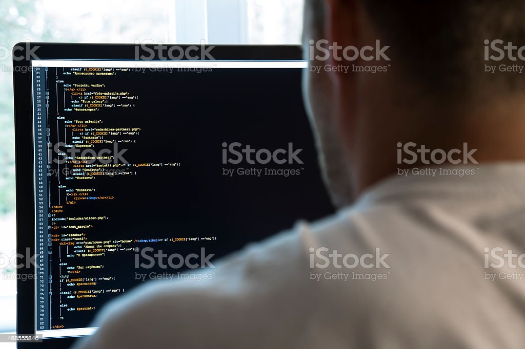 programmer from behind and programming code on computer monitor stock photo