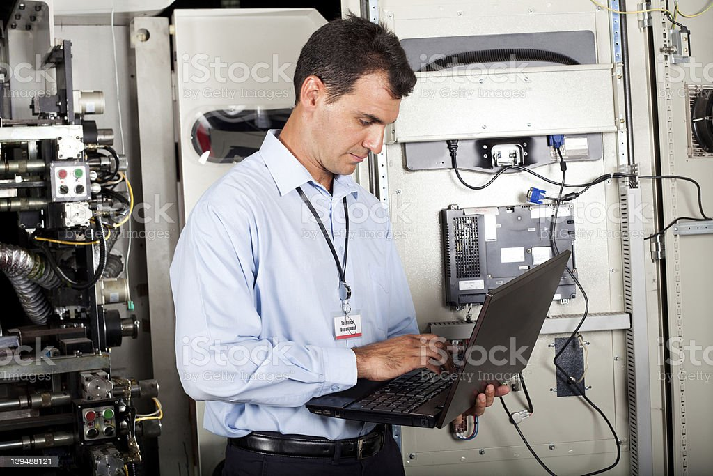 Programmer holding laptop and checking machine stock photo