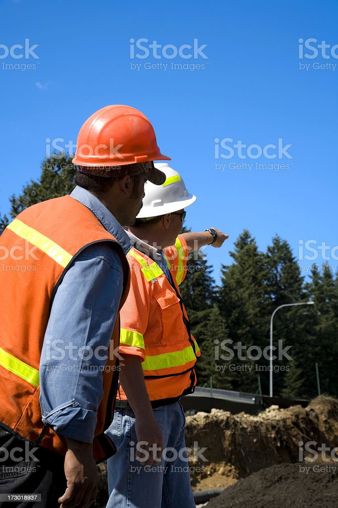 Project Manager overseeing Erosion control 'series' safety orange helmet pointing royalty-free stock photo