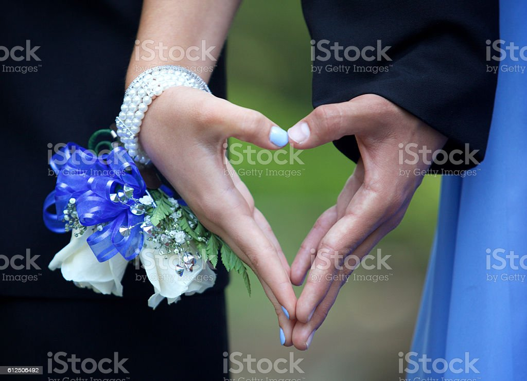 Prom Couple Forming a Heart with their Hands  Close Up stock photo