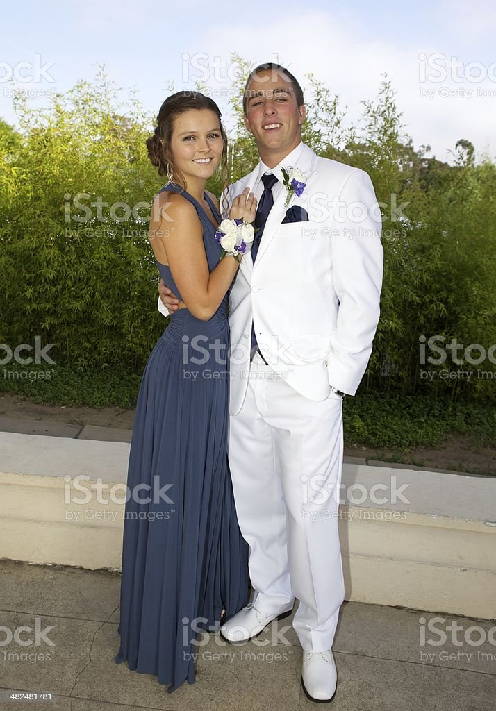 Prom Couple Posing in Blue Dress and White Tuxedo royalty-free stock photo