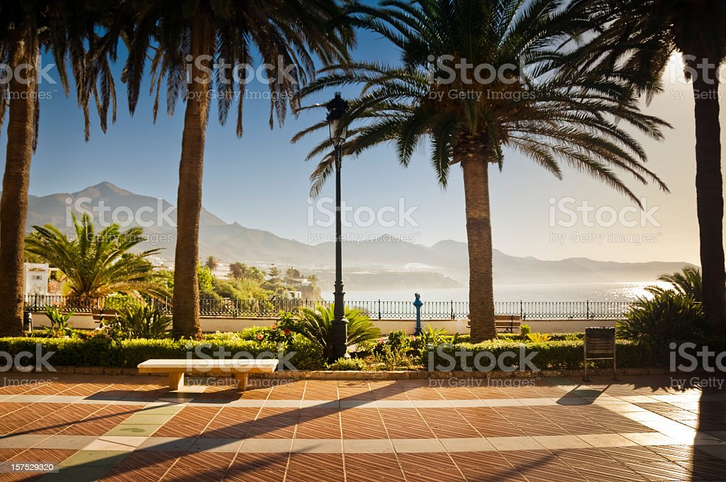 Promenade in Nerja with palm trees, a bench and mountains stock photo