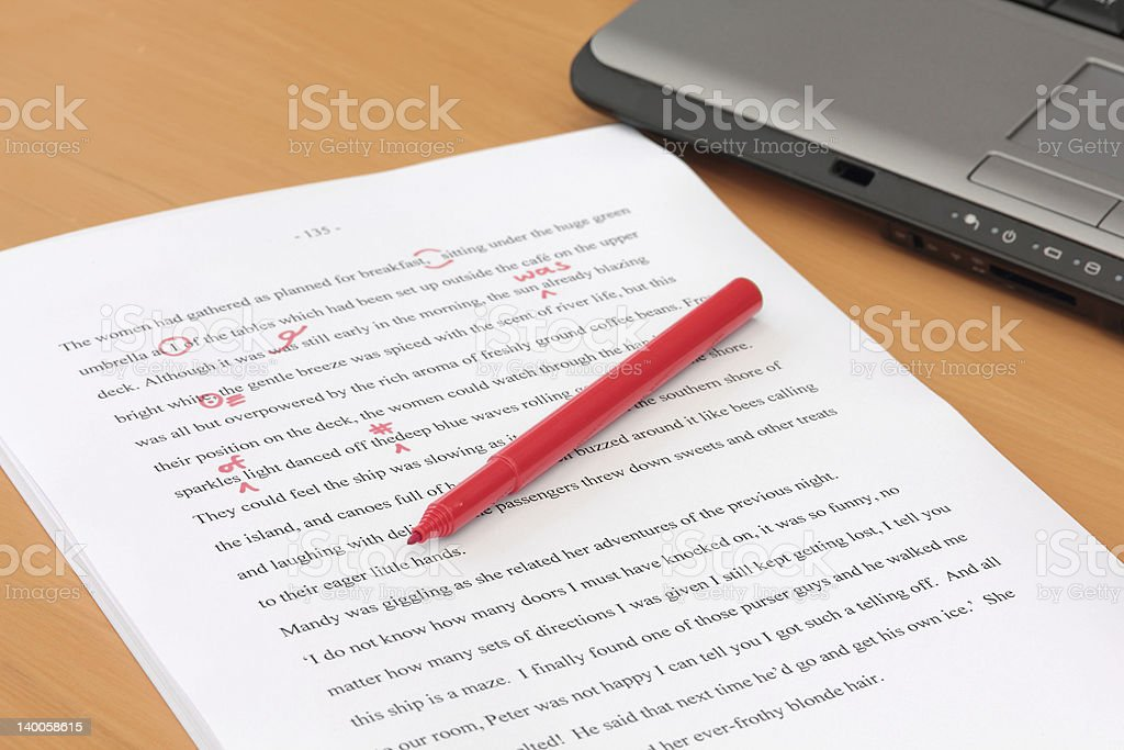 Proofreading a Manuscript beside Laptop stock photo