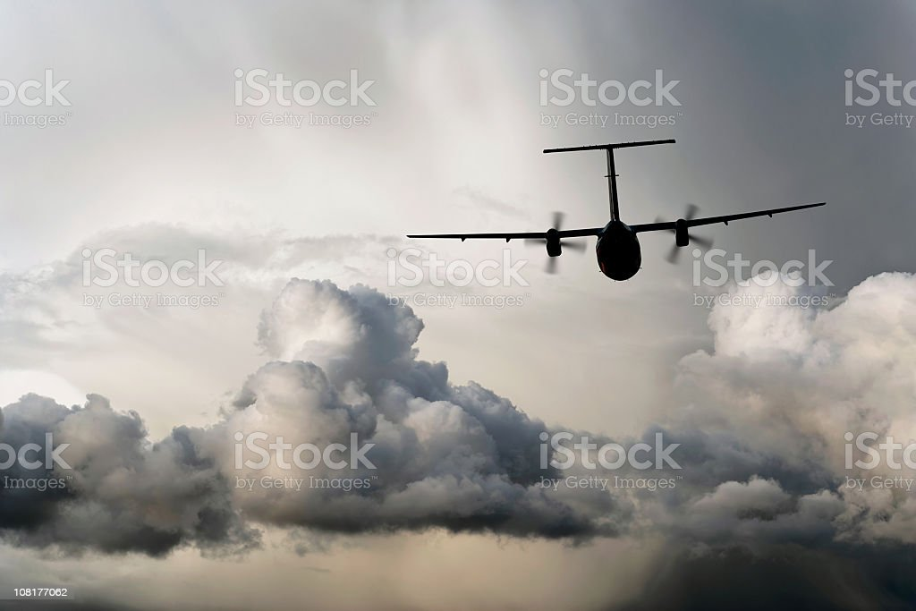 propeller airplane flying in storm stock photo