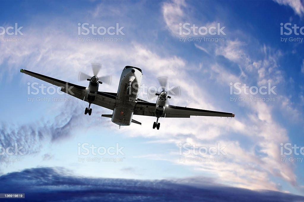 XL propeller airplane landing at sunset royalty-free stock photo